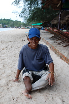 Landmine victim begging on the beach